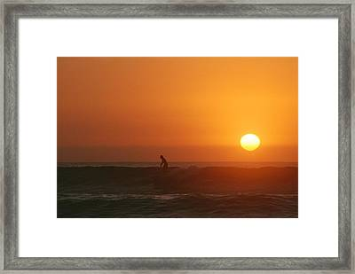 A Man Surfs As The Sun Sets Framed Print by Jimmy Chin
