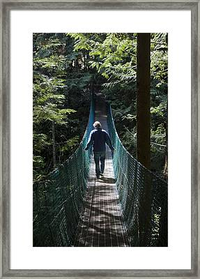 A Man Walks Across A Suspension Bridge Framed Print by Taylor S. Kennedy