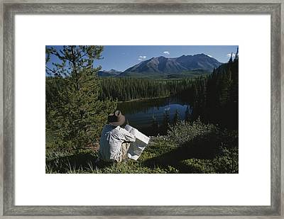 A Man With A Cowboy Hat Reads A Map Framed Print