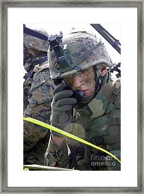 A Marine Communicates Over The Radio Framed Print by Stocktrek Images
