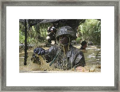 A Marine Splashes As He Makes His Way Framed Print by Stocktrek Images