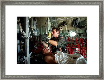 A Medic Adjusts The Intravenous Drip Framed Print by Everett
