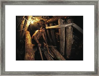 A Miner Works His Way Through A Jumble Framed Print by Randy Olson