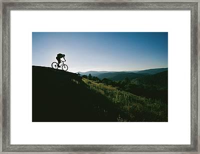 A Mountain Biker Heads Down A Hill Framed Print by Skip Brown