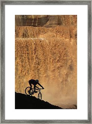 A Mountain Biker Pedals Past Rushing Framed Print by Bill Hatcher