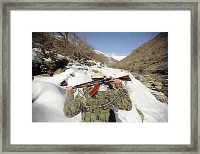 A Mujahadeen Guard Walks With U.s Framed Print by Stocktrek Images