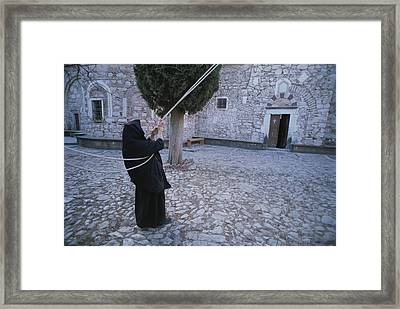 A Nun Pulls On Ropes In A Courtyard Framed Print by Tino Soriano