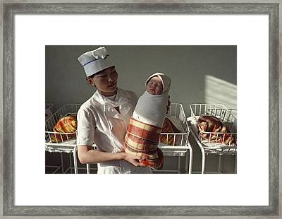 A Nurse Holds A Tightly Wrapped Newborn Framed Print by Dean Conger