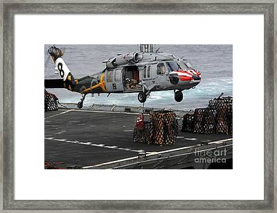 A Sailor Hooks Cargo To An Mh-60s Sea Framed Print by Stocktrek Images