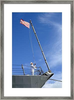 A Sailor Lowers The U.s. Navy Jack Framed Print