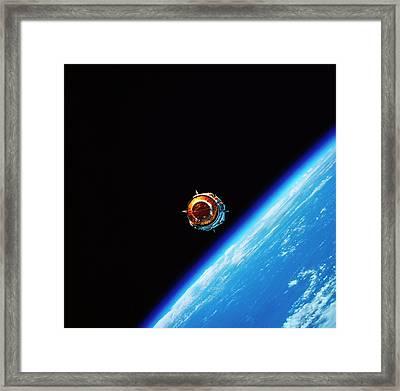 A Satellite In Orbit Above Earth Framed Print by Stockbyte