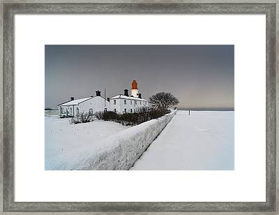 A Snow Covered Fence With A Lighthouse Framed Print by John Short