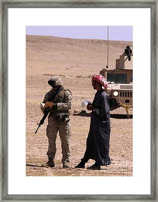 A Soldier Communicates With A Local Framed Print by Stocktrek Images