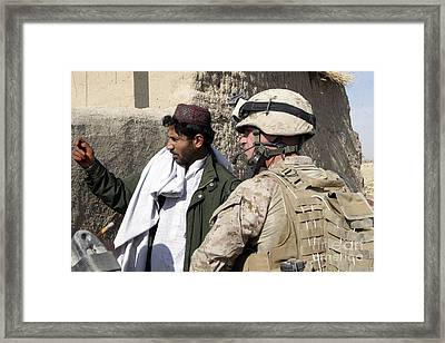 A Soldier Talks To A Local Villager Framed Print