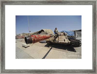 A T-55 Tank With Two Children Playing Framed Print by Andrew Chittock