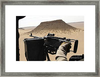 A Uh-60 Blackhawk Crew Chief Holds An Framed Print by Stocktrek Images