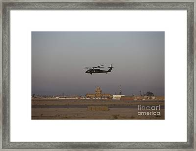A Uh-60 Blackhawk Helicopter Flies Framed Print