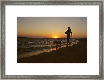 A Woman And Her Dog Running Framed Print by Skip Brown