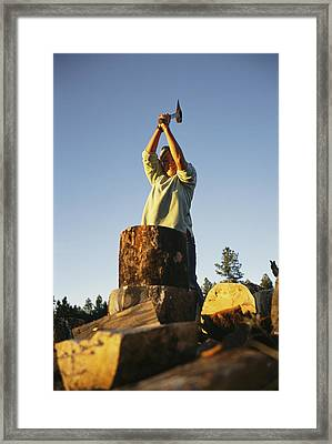 A Woman Chops Wood With Framed Print by Bobby Model