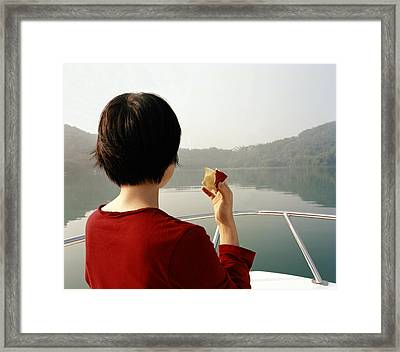 A Woman Eats An Apple While Riding Framed Print by Justin Guariglia
