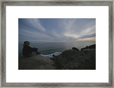A Woman In A Hat Sits On Cliff Looking Framed Print by Todd Gipstein