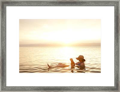 A Woman Reads A Book While Floating Framed Print by Taylor S. Kennedy