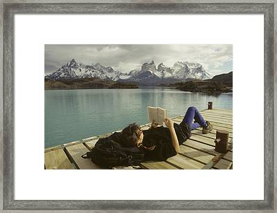 A Woman Relaxes On A Dock While Reading Framed Print