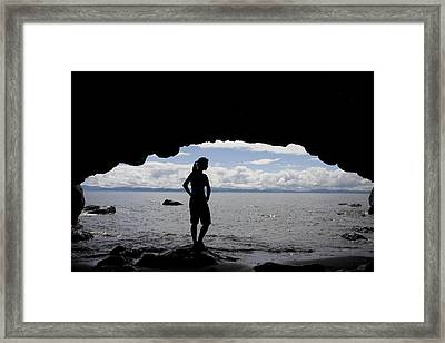 A Woman Stands Silhouetted In A Cave Framed Print