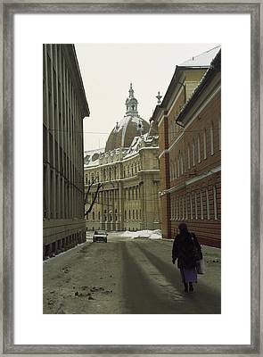 A Woman Walks Down A Snowy  Street Framed Print by Gordon Wiltsie