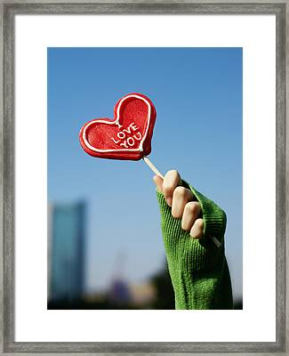 A Womans Hand Holding Up A Red Framed Print by Justin Guariglia