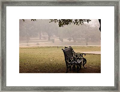 Framed Print featuring the photograph A Wrought Iron Black Metal Bench Under A Tree In The Qutub Minar Compound by Ashish Agarwal