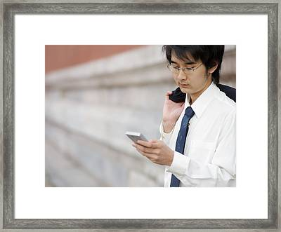 A Young Businessman Checks His Text Framed Print by Justin Guariglia