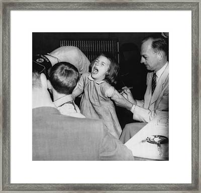 A Young Girl Receiving A Vaccine Framed Print by Everett