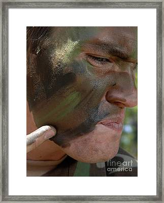 Airman Applies War Paint To His Face Framed Print by Stocktrek Images