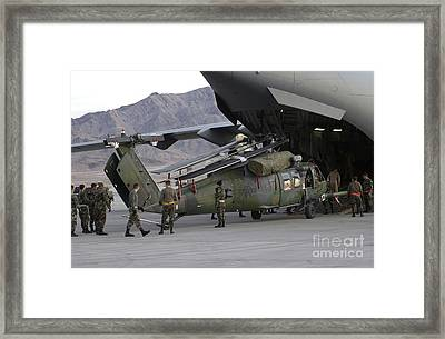Airmen Load An Hh-60 Pave Hawk Framed Print by Stocktrek Images