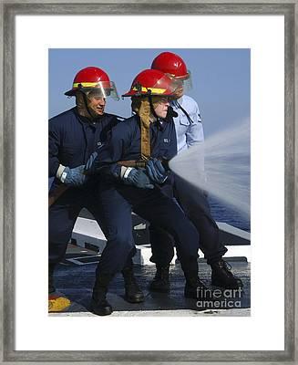Airmen Participate In A Fire Hose Team Framed Print