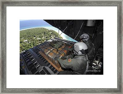 Airmen Push Out A Pallet Of Donated Framed Print by Stocktrek Images