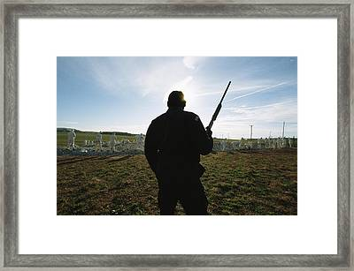 An Armed Guard Watches Over Inmates Framed Print by Bill Curtsinger