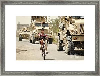 An Iraqi Boy Rides His Bike Past A U.s Framed Print by Stocktrek Images