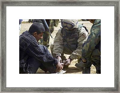 An Iraqi Detainee Receives A Band-aid Framed Print by Everett