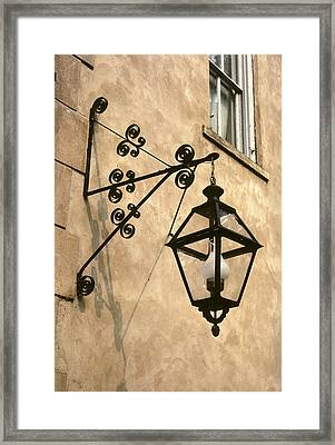 An Iron Street Lamp Hangs Framed Print by Rex A. Stucky