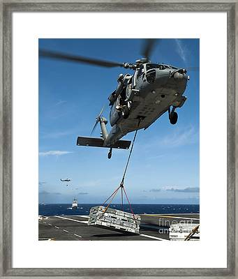 An Mh-60s Sea Hawk Helicopter Lowers Framed Print by Stocktrek Images