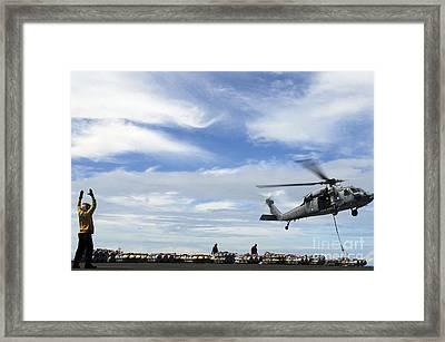 An Mh-60s Sea Hawk Lifts A Pallet Framed Print by Stocktrek Images