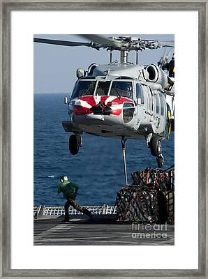 An Mh-60s Sea Hawk Picks Up Pallets Framed Print by Stocktrek Images