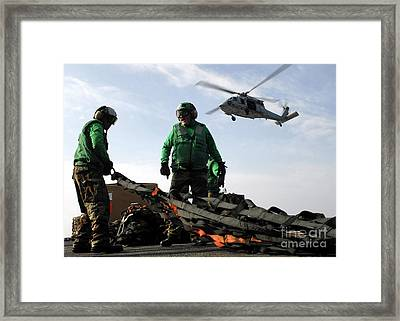 An Mh-60s Seahawk Passes Over Two Framed Print by Stocktrek Images
