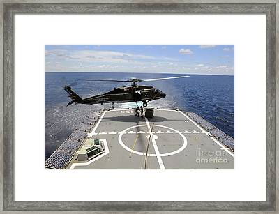 An Sh-60f Sea Hawk Helicopter Lowers Framed Print