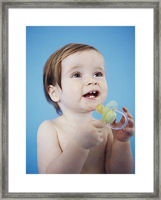 Baby Girl Holding A Dummy Framed Print by Ian Boddy