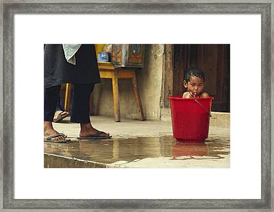 Bhutanese Boy Bathing In A Bucket Framed Print