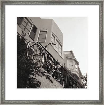 Bike Locked On Fence Against House Framed Print by Copyright Ricky G. Brown 2011