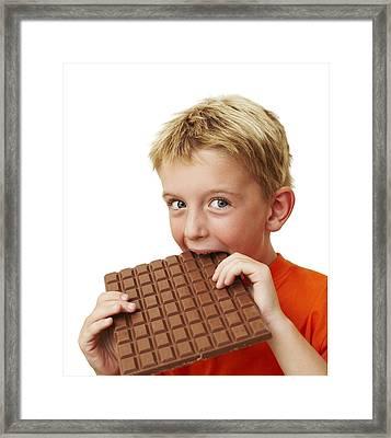 Boy Eating Chocolate Framed Print by Ian Boddy
